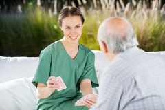 Smiling Female Nurse Playing Cards With Senior Man Royalty Free Stock Photos