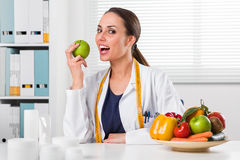 Smiling Female nutritionist eating a Green Apple in her office. Smiling Female nutritionist with tape measure around her neck eating a Green Apple in her office Stock Image