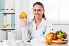 Female nutritionist holding an Orange slice. Smiling Female nutritionist in her office holding an Orange slice and showing healthy vegetables and fruits Stock Photo