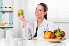 Female nutritionist holding a green apple. Smiling Female nutritionist holding a green apple and showing healthy vegetables and fruits in her office; Healthcare Stock Images