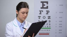Smiling female oculist writing test results and smiling, good treatment results. Stock footage stock footage