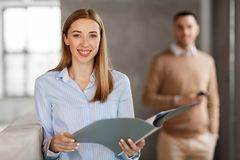 Smiling female office worker with folder Stock Photo