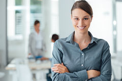 Smiling female office worker portrait. Smiling female office worker posing with arms crossed and looking at camera, office interior on background Royalty Free Stock Photos