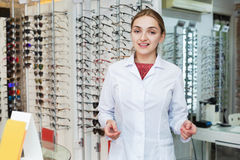 Smiling female optician offering professional help in  shop Stock Image