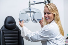 Smiling female optometrist adjusting phoropter Stock Photos