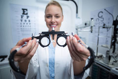 Smiling female optometrist holding messbrille Royalty Free Stock Photography