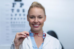 Smiling female optometrist holding spectacles Stock Image