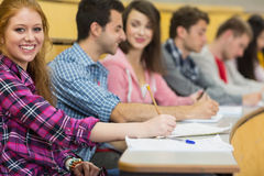 Smiling female with other students writing notes at lecture hall Royalty Free Stock Photos
