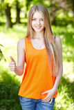 Smiling female outdoors gesturing thumb up Royalty Free Stock Photos