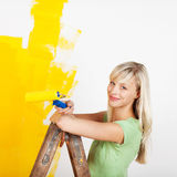 Smiling female painting yellow Royalty Free Stock Photos