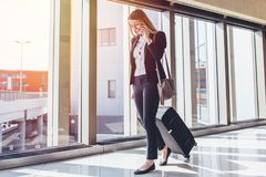 Smiling female passenger proceeding to exit gate pulling suitcase through airport concourse while talking on the phone.  Royalty Free Stock Images