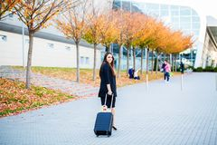 Smiling female passenger proceeding to exit gate pulling suitcase through airport concourse royalty free stock image