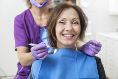 Smiling Female Patient With Dentist Holding Tools Stock Photography