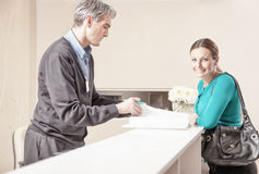 Smiling female patient in 40s received by male doctor at hospita Royalty Free Stock Photography