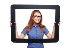 Smiling female peeping out of tablet frame Royalty Free Stock Photography