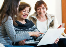 Smiling female pensioners and relative browsing web on laptop Royalty Free Stock Photography