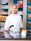 Smiling female pharmacist in drugstore Stock Images