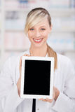 Smiling female pharmacist holding a blank tablet Stock Images