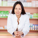 Smiling female pharmacist leaning on counter Royalty Free Stock Images