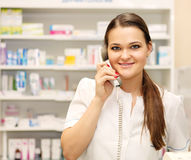 Smiling female pharmacist on the phone at drugstore Stock Image
