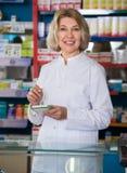 Smiling female pharmacist posing in drugstore Stock Photos