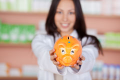 Smiling female pharmacist showing piggybank Royalty Free Stock Photos