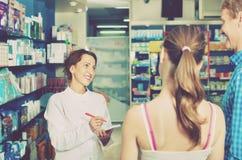 Smiling female pharmacist wearing uniform working Stock Photo
