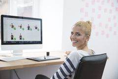 Smiling female photo editor sitting at the table Royalty Free Stock Image