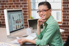Smiling female photo editor using computer in office. Portrait of smiling female photo editor using computer in the office Stock Photography