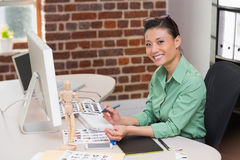 Smiling female photo editor using computer in office. Portrait of smiling female photo editor using computer in the office Royalty Free Stock Photography
