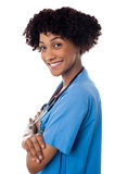 Smiling female physician standing sideways with folded arms Stock Photo