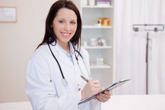 Smiling female physician taking notes Stock Photo