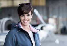 Smiling female pilot posing in the hangar Royalty Free Stock Photography