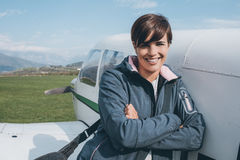 Smiling female pilot posing with her plane. Smiling cheerful female pilot leaning on a propeller airplane and posing, blue sky on the background, travel and royalty free stock photo