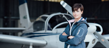 Smiling female pilot posing with her plane Stock Photo