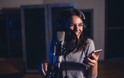 Female singer singing in recording studio royalty free stock image