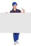 Smiling female plumber holding placard Stock Photo