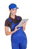 Smiling Female Plumber Working On Digital Tablet Royalty Free Stock Images
