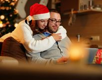 Smiling female and plump male using laptop on christmas. Smiling female in Santa`s hat and plump positive male using a laptop on a couch in a room with Royalty Free Stock Images