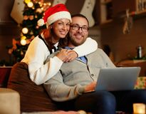 Smiling female and plump male using laptop on christmas. Smiling female in Santa`s hat and plump positive male using a laptop on a couch in a room with Stock Photography