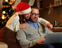 Smiling female and plump male using laptop on christmas. Smiling female in Santa`s hat and plump positive male using a laptop on a couch in a room with Royalty Free Stock Photo