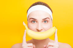 Smiling female portrait holding a banana. Before her mouth on yellow studio background Royalty Free Stock Images