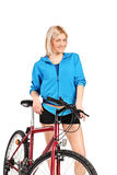 A smiling female posing next to a bicycle Royalty Free Stock Photo