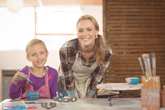 Smiling female potter and girl painting in pottery workshop Stock Photo