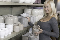 Smiling female in pottery shop. Smiling young customer looking at pottery at a florist shop Royalty Free Stock Photo