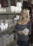 Smiling female in pottery shop. Smiling young customer looking at pottery at a florist shop stock photography