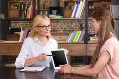 smiling female psychiatrist showing digital tablet and pointing on screen to female patient stock image
