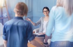 Smiling female psychologist greeting new teenage patient and his mom. Please sit here. Young professional wearing glasses looking at a family standing in front Royalty Free Stock Images