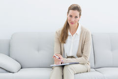 Smiling female psychologist sitting on sofa Stock Photo