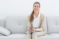 Smiling female psychologist sitting on sofa Stock Image